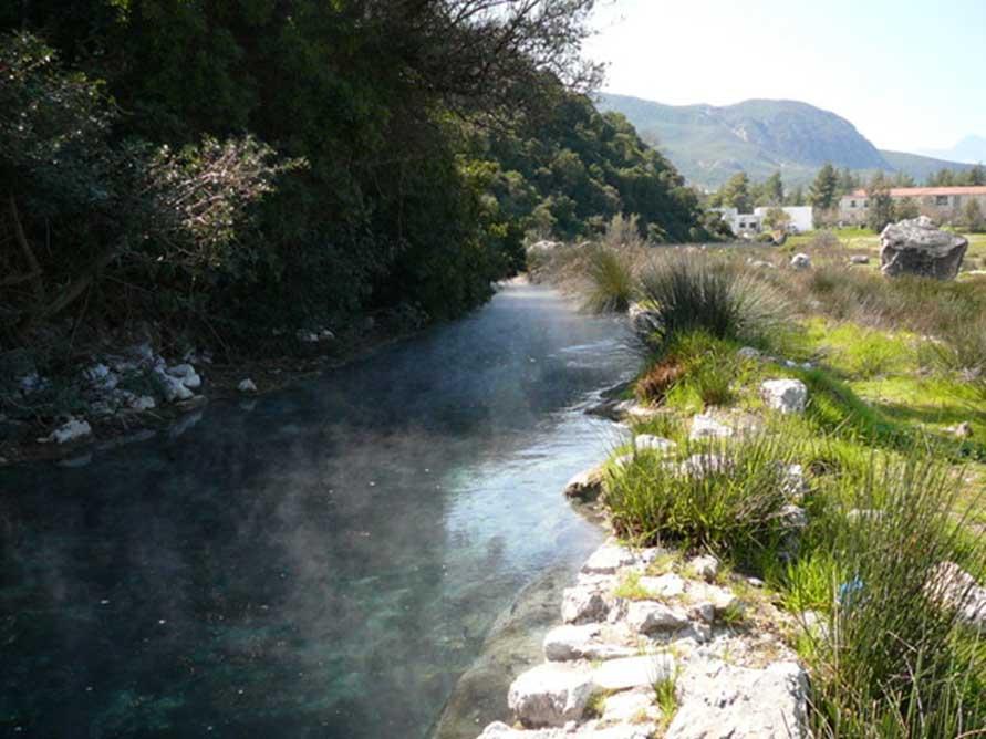 Termópilas debe la mitad de su nombre a sus aguas termales. Este río está formado por agua hirviendo que huele a azufre. Al fondo se pueden ver los edificios de los modernos baños termales. En la antigüedad, los manantiales crearon un pantano. (CC BY SA 3.0)