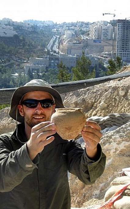 Alex Wigman, arqueólogo de la Autoridad de Antigüedades de Israel, muestra una pequeña vasija hallada en la tumba cananea descubierta en Jerusalén en el año 2014. (Shua Kisilevitz, Autoridad de Antigüedades de Israel)