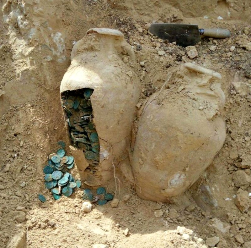 Dos de las ánforas repletas de monedas romanas durante su proceso de extracción (Fotografía: El País/Europa Press)