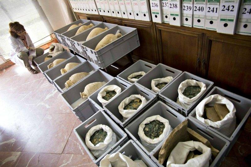 Parte de las ánforas y monedas halladas por los operarios de una obra en la población española de Tomares (Sevilla). (Fotografía: Paco Puentes/El País)