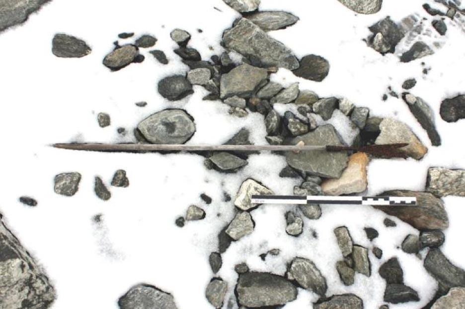 Flecha del 800 d. C. hallada en el suelo de un glaciar en Noruega, cubierta aún en parte por la nieve. (Espen Finstad, 'Secretos del hielo', Consejo del Condado de Oppland)