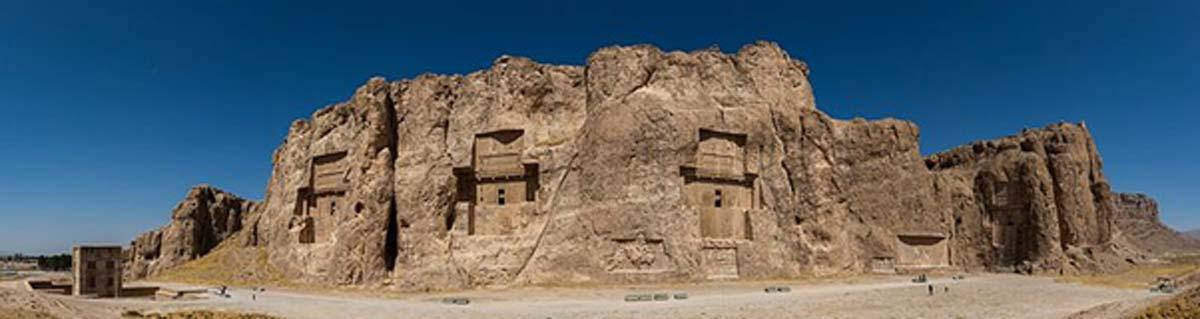 Vista panorámica de la antigua necrópolis de Naqsh-e Rustam, situada en la provincia iraní de Fars, Irán. El monumento incluye relieves grabados en la roca de los períodos aqueménida y sasánida, cuatro tumbas de reyes aqueménidas y el Cubo de Zoroastro (extremo izquierdo de la fotografía). (Diego Delso/CC BY SA)