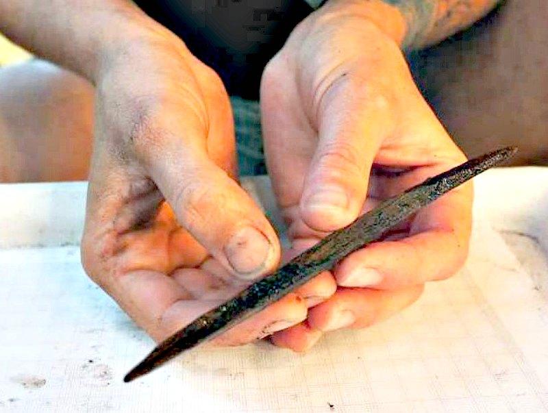 Uno de los arqueólogos del equipo científico sostiene entre sus manos un artefacto con dos puntas tallado en madera de 7.000 años de antigüedad. Este artefacto podría haber sido utilizado como anzuelo para capturar peces. (Fotografía: Código Oculto/Angela Dick).