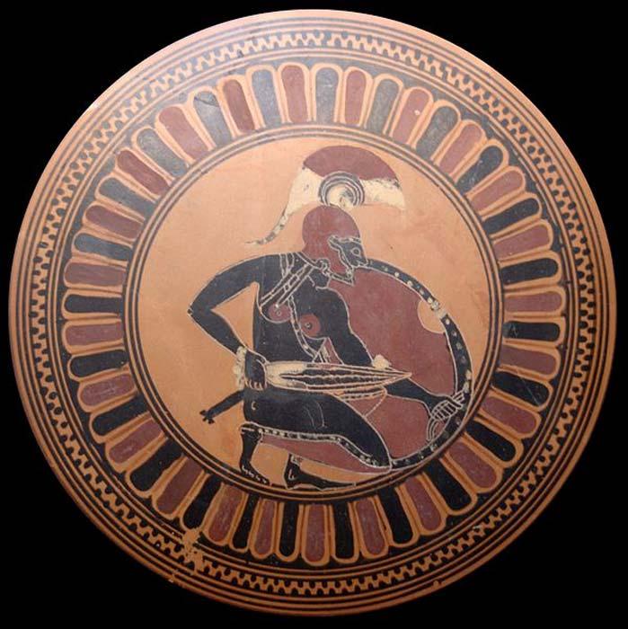 Guerrero de la antigua Grecia arrodillado y con su espada desenvainada – posiblemente Aquiles esperando a Troilo. Tondo de un kílix ático de figuras negras, ca. 560 a. C. (Dominio público) Los guerreros griegos debían conseguir las armas por sus propios medios.