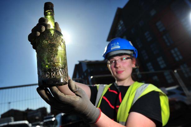 La arqueóloga Rosie Banens muestra una de las antiguas botellas de licor halladas en las ruinas del antiguo pub. (Manchester Evening News)