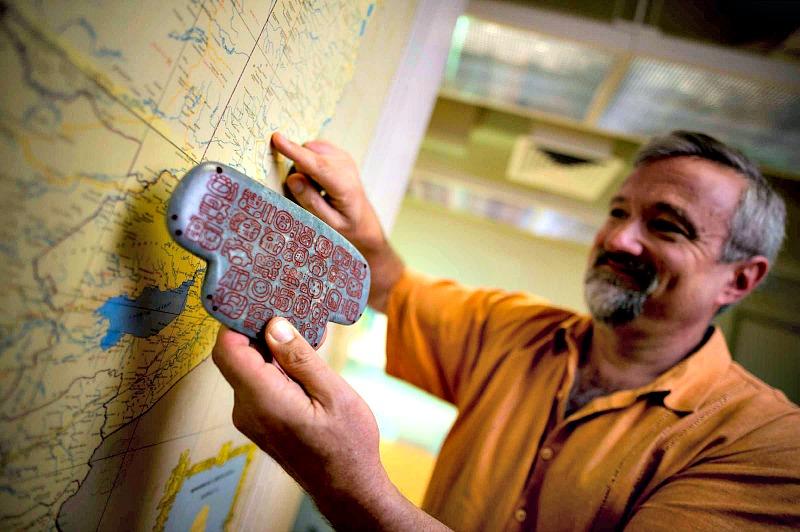 El arqueólogo Geoffrey Braswell, sosteniendo una réplica del colgante de jade maya. (Fotografía: Erik Jepsen/UC San Diego Publications)