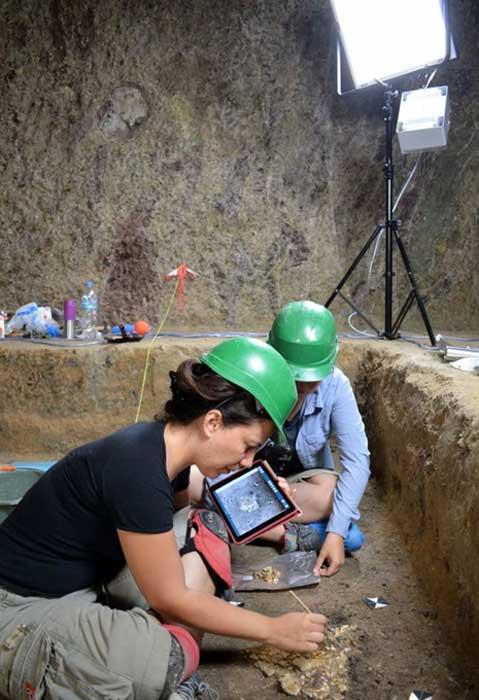 Arqueólogos registrando los huesos hallados en el interior de la cámara funeraria. (Ministerio de Cultura griego)