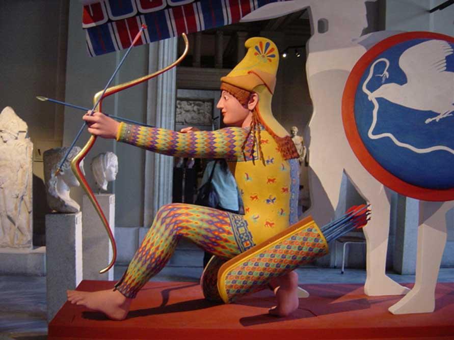 """Arquero troyano (conocido como """"Paris""""), figura W-XI del frontón occidental del Templo de Afea, ca. 505-500 a. C., reconstrucción polícroma realizada para la exposición 'Bunte Götter' (""""Dioses en color""""). (CC BY-SA 2.5)"""
