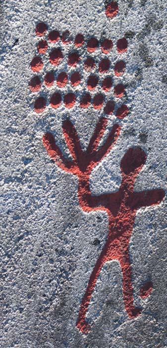 Figura humana y cazoletas. La profundidad de los grabados es claramente visible a la luz del atardecer. Arte rupestre de Tanum, Suecia. (CC BY SA 3.0)