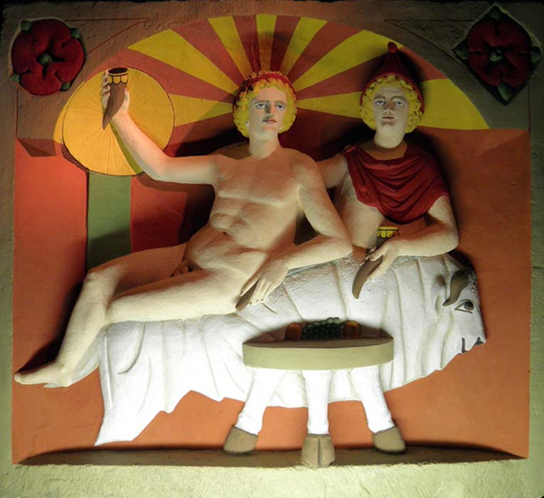Reproducción de una escultura en la que Mitra y el dios sol participan de un banquete sentados sobre una piel de toro. (CC BY-SA 2.0)