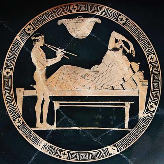 Escena de un banquete: un hombre adulto se reclina sobre un diván mientras un joven muchacho toca el aulós, instrumento de viento de la antigua Grecia. Tondo de una copa ática de figuras rojas (Dominio público).