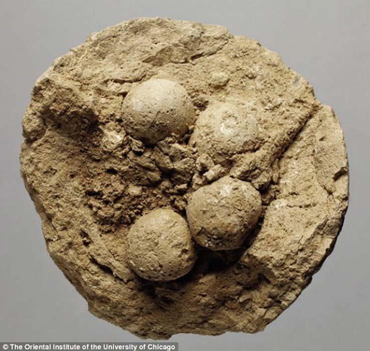 Fotografía de una de las bolas de arcilla mesopotámicas, partida por la mitad, en cuyo interior se observan elementos de menor tamaño (contadores o 'fichas') (Fotografía: Instituto Oriental de la Universidad de Chicago)