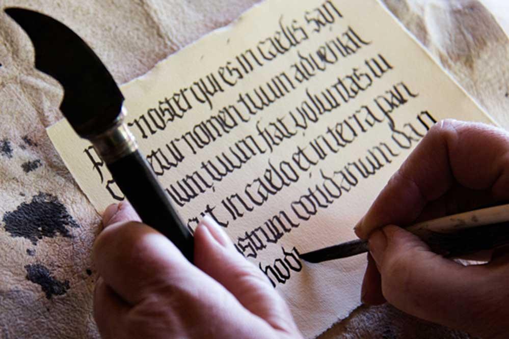 Calígrafo escribiendo en texto de estilo medieval. (CC BY-ND 2.0)