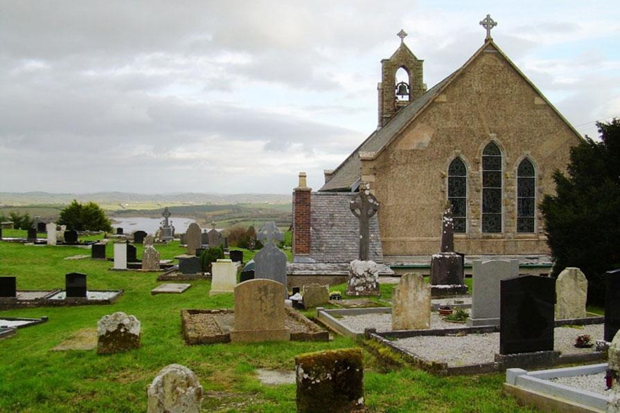 El cementerio de la Iglesia del Sagrado Sorazón de Boho, donde se encuentra la tumba del Reverendo James McGirr con su 'tierra curativa' (Dominio público)