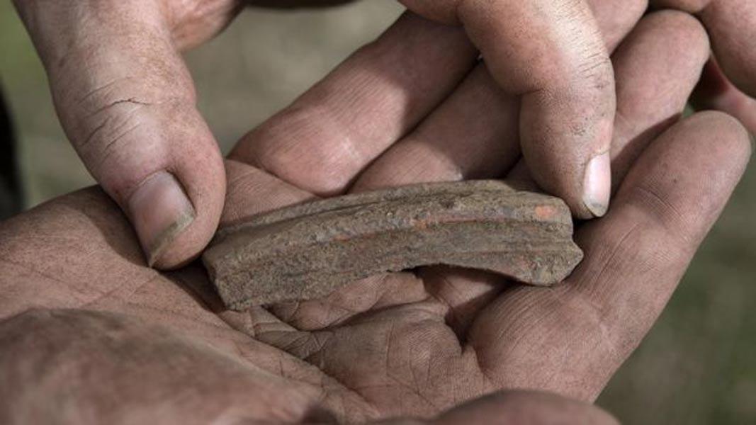 Ryan Smith (supervisor de excavaciones) muestra un fragmento de cerámica fenicia de engobe rojo procedente de Turquía occidental. (Emily Whitfield-Wicks)