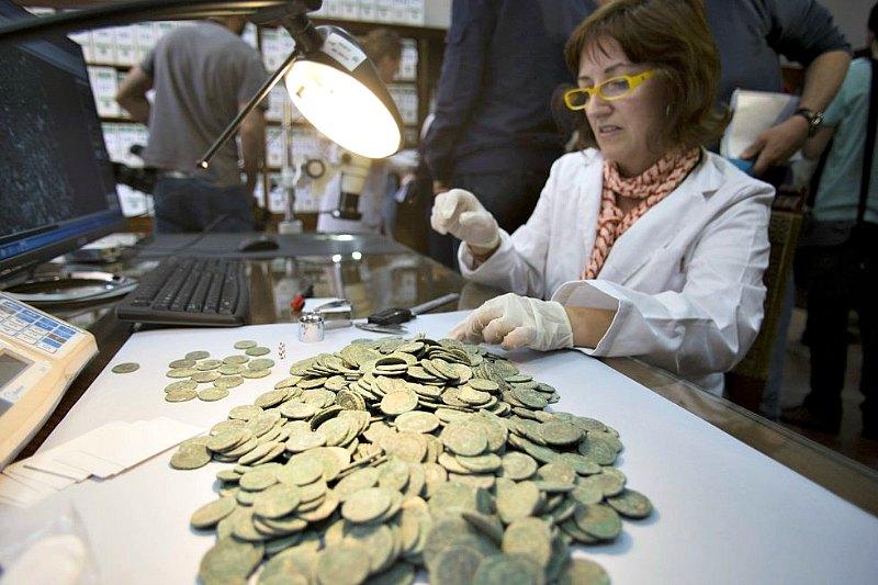 Científicos del Museo Arqueológico de Sevilla están llevando a cabo el estudio de las monedas halladas recientemente en Tomares. (Fotografía: El País/Paco Puentes)