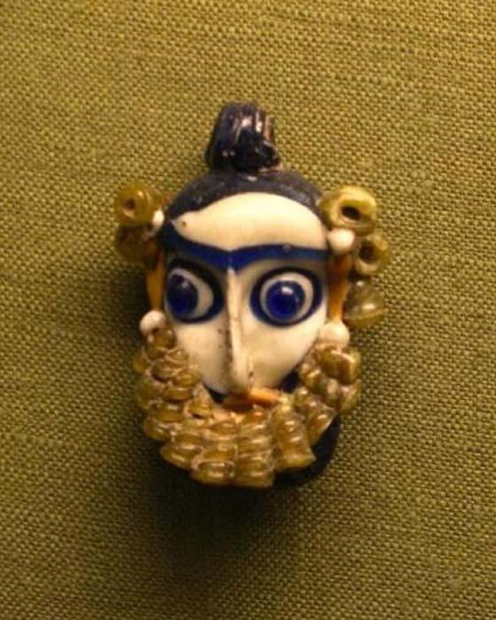 Colgante fenicio con forma de cabeza barbada y decorado con cuentas de vidrio (siglos IV a. C. – III a. C.) (Dominio público)