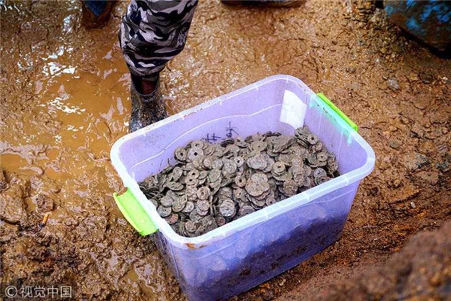 En este contenedor podemos ver algunas de las monedas halladas durante las obras de construcción realizadas en una casa de la provincia china de Jiangxi. (VCG)