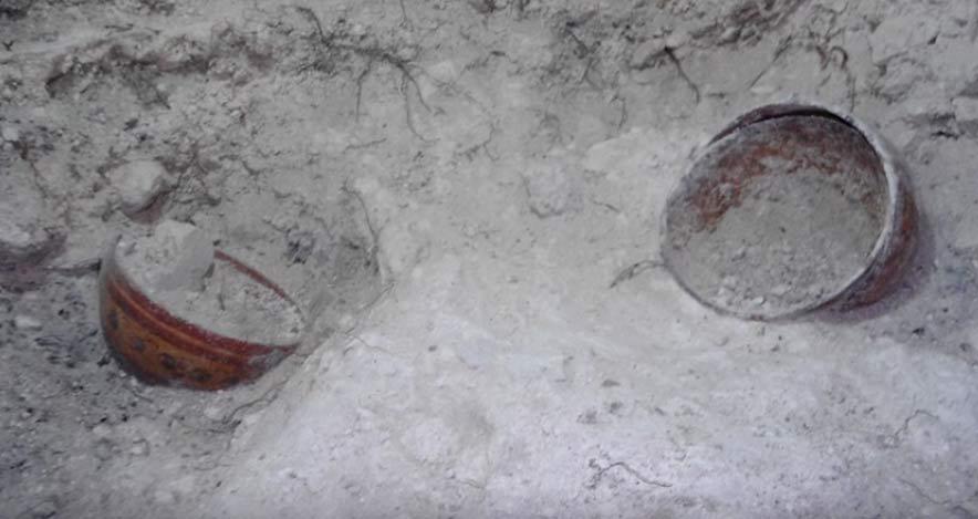 Se encontraron cuatro cuencos policromados en el interior de la cámara funeraria, uno de ellos con el nombre de un rey maya. Fuente: Fotograma del vídeo de la USC.