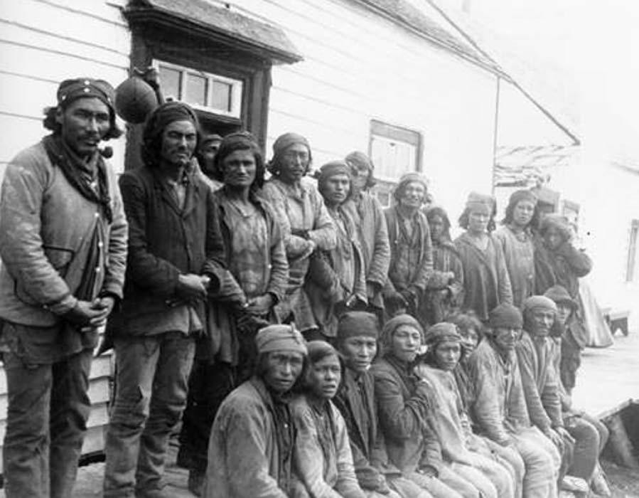 Davis Inlet, agosto de 1903. Comerciantes Innu se reúnen en el exterior de un establecimiento de la Compañía de la Bahía de Hudson situado en Davis Inlet, Labrador. Public License.