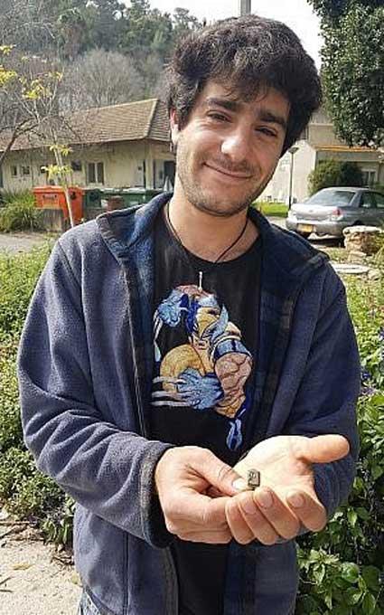 El jardinero Dekel Ben-Shitrit con el anillo que encontró mientras desbrozaba. (Nir Distelfeld, Autoridad de Antigüedades de Israel)