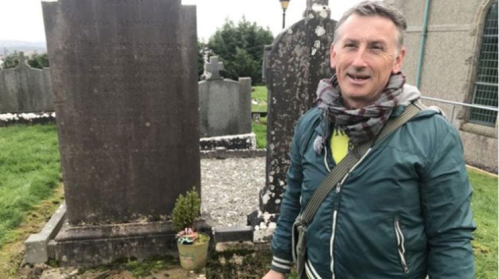 El Dr. Gerry Quinn en la tumba del Reverendo James McGirr (Crédito: BBC)