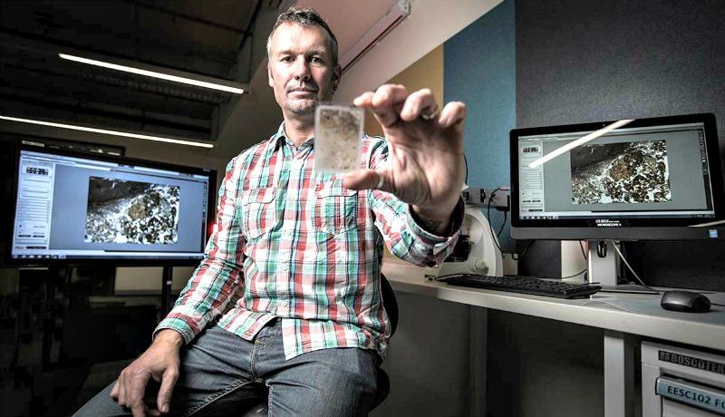 El Dr. Mike Morley, de la Universidad de Wollongong, Australia, con una muestra de sedimentos obtenida en Liang Bua. La muestra contiene nuevas y determinantes evidencias que revelan que humanos modernos (Homo sapiens) encendían fuegos con toda probabilidad en Liang Bua hace 41.000 años. (Fotografía: UOW)