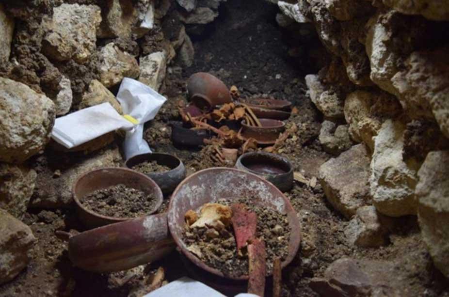 El Enterramiento 80 durante las excavaciones: en el centro se observa una copa de piedra rodeada de huesos. (Proyecto Arqueológico Waka' y Ministerio de Cultura y Deportes de Guatemala)