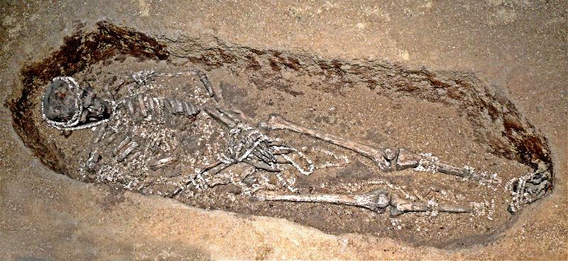 Enterramiento paleolítico de un varón adulto (28.000-30.000 años de antigüedad), luciendo diversos ornamentos, situado en el yacimiento ruso de Sunghir. Este yacimiento contiene varios enterramientos espectaculares que revelan las primeras pruebas de ritos funerarios complejos en forma de ajuares depositados junto con los muertos. (Public Domain)