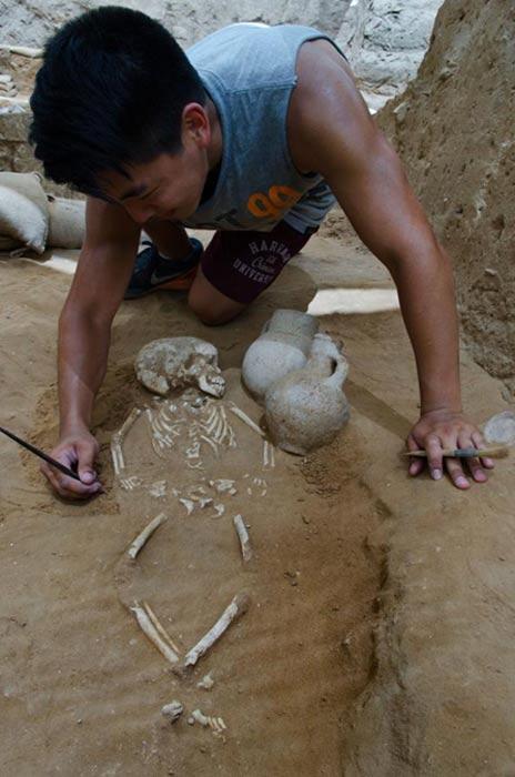 Excavaciones de la tumba de un niño en Ascalón. Los escasos niños enterrados en este cementerio aparecían cubiertos por una capa de fragmentos de piezas cerámicas rotas. Fotografía: Melissa Aja para la Expedición Leon Levy en Ascalón