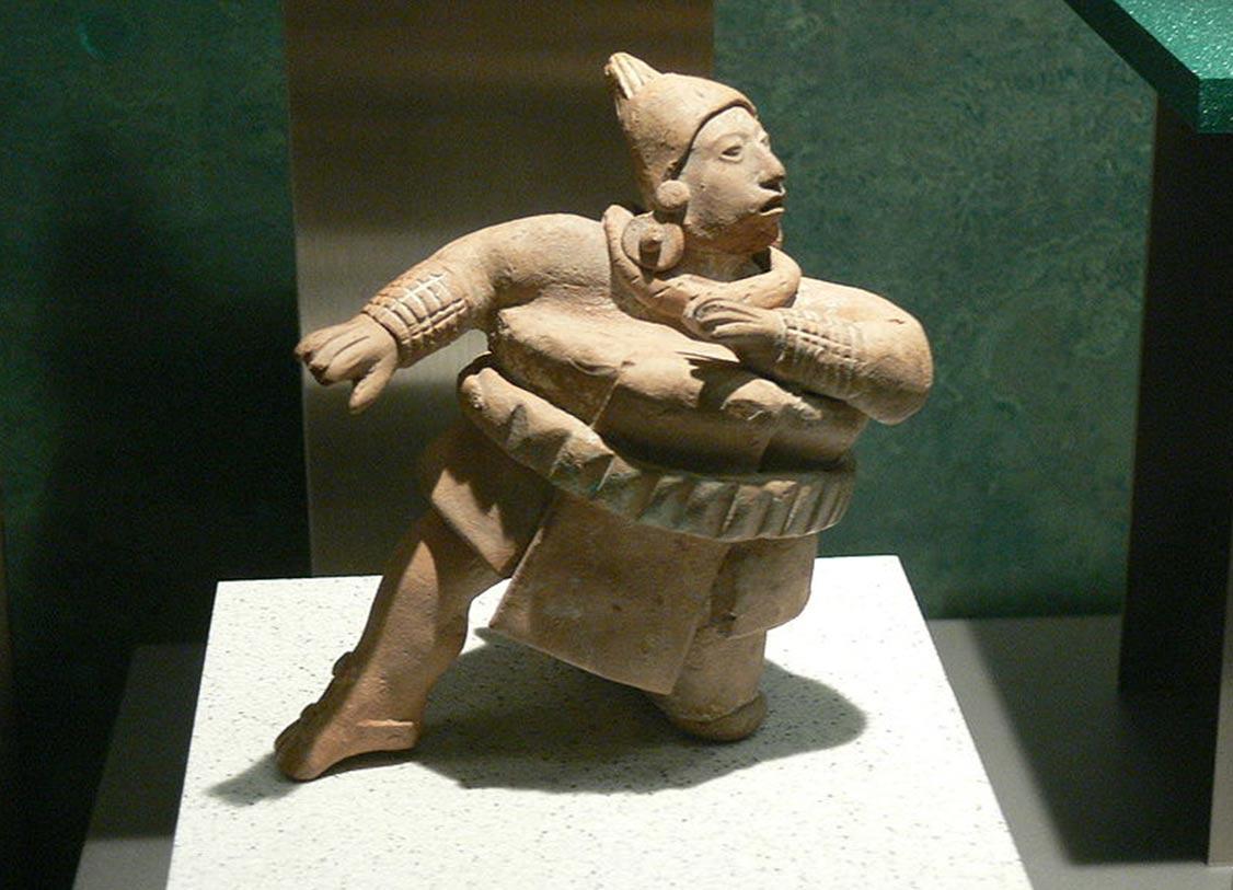 Estatuilla de un jugador de pelota luciendo gruesa ropa acolchada (Wikimedia Commons)