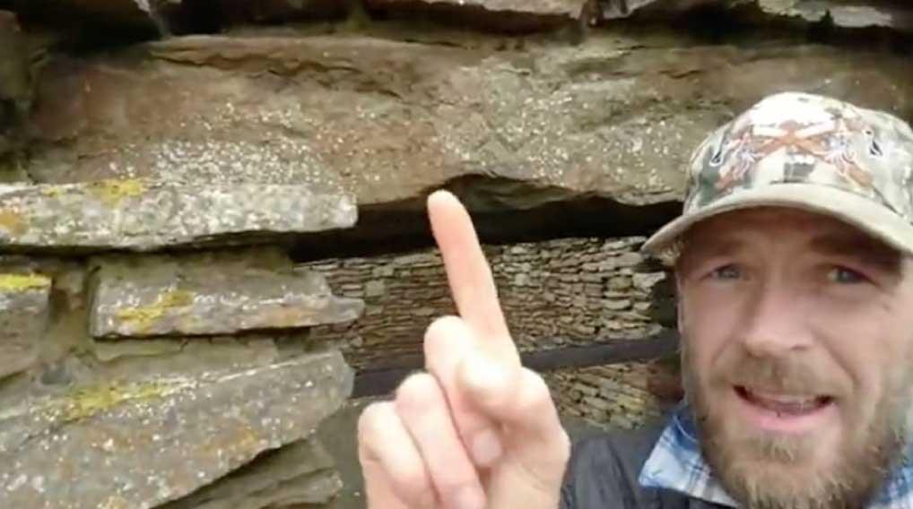 El autor del artículo señala una esvástica grabada sobre un dintel de piedra en el castillo de Old Wick ubicado en Caithness, Escocia. 18 de julio del 2018. (Imagen: Cortesía de Ashley Cowie)