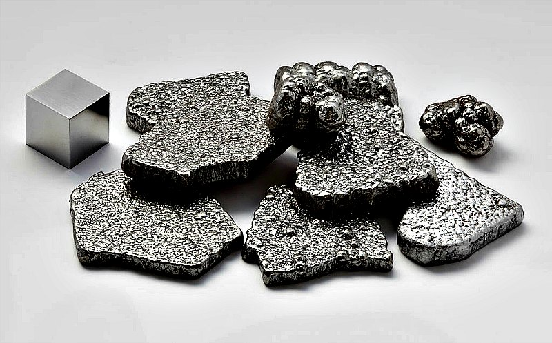 Fragmentos de hierro puro (99.97 %+), refinado electrolíticamente, junto a un cubo de 1 cm3 de hierro de alta pureza (99.9999 %). (Public Domain)