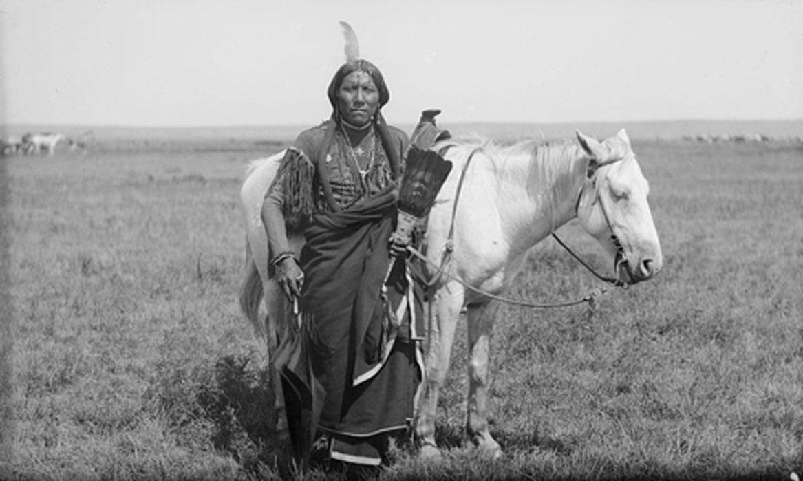 """Guerrero comanche llamado """"Ako"""" fotografiado con su caballo en 1892. (Dominio público)"""
