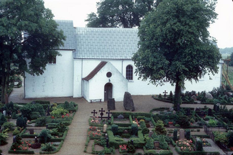 La actual iglesia de Jelling con las piedras rúnicas ante una de sus puertas. (Jerrye & Roy Klotz MD/CC BY SA 3.0)