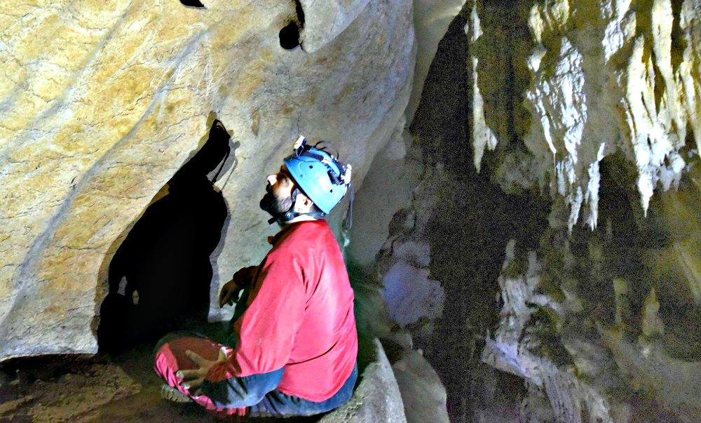 Miembro del equipo investigador contemplando algunos de los grabados rupestres recientemente descubiertos. (Fotografía: El País)