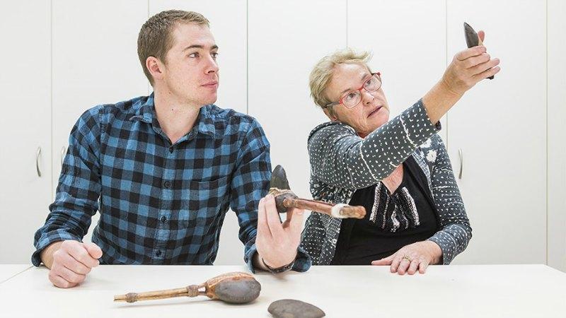 Los investigadores y profesores de la Universidad Nacional de Australia Tim Maloney y Sue O'Connor examinando hachas y otras antiguas herramientas semejantes al hacha recién descubierta. (Fotografía: Stuart heno/ANU)
