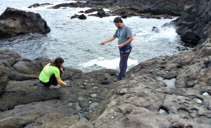 Dos de los investigadores estudiando los conjuntos de cazoletas descubiertos en la Punta del Moro (Mazo, La Palma).(Fotografía: eldiario.es)
