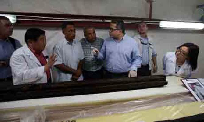 Khaled El-Enany, Sakuji Yoshimora, y Eissa Zidan inspeccionan el antiguo tablón en el laboratorio. (Ahram Online)