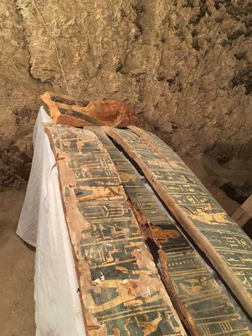 La máscara y parte del ataúd de madera hallados en la tumba. Crédito: Ahram Online
