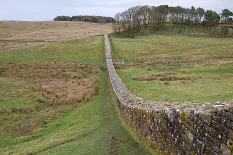 Tramo del Muro de Adriano que se extiende colina abajo desde la esquina noreste del fuerte romano de Housesteads. (Dominio público)