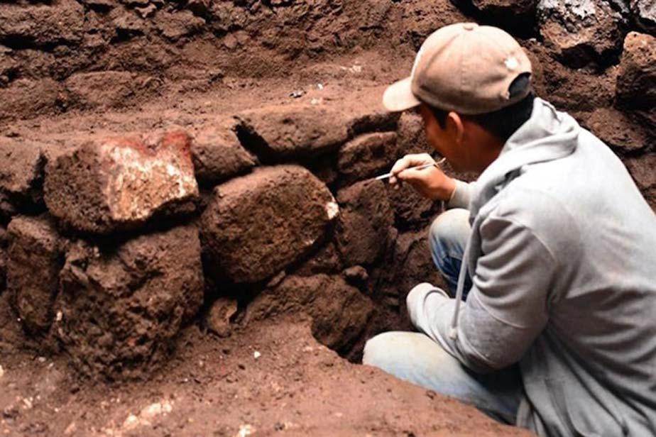 Arqueólogo examina los muros del recientemente descubierto templo de la época azteca. (Melitón Tapia/INAH)