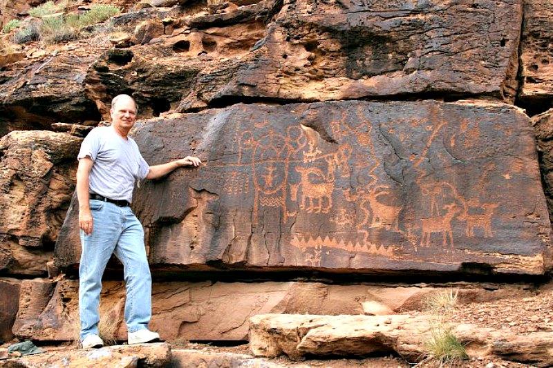 John A. Ruskamp ante algunos petroglifos hallados en Utah, Estados Unidos, cercanos a los que presentan antigua escritura china, según él mismo defiende. (Fotografía: Cortesía de John A. Ruskamp/La Gran Época)