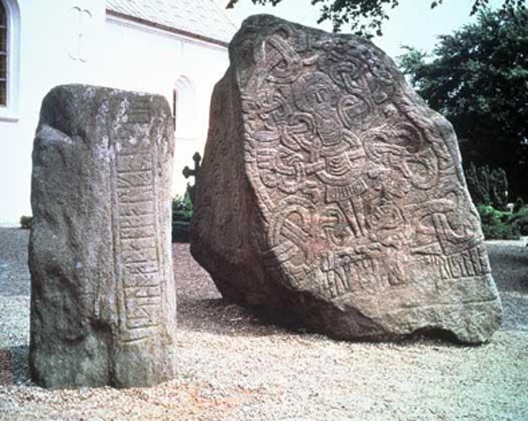 La piedra rúnica de Harald con la imagen de Cristo se alza ante la Iglesia de Jelling. Junto a ella se encuentra la piedra de su padre Gorm creada para la reina Thyra, madre de Harald. (Nationalmuseet - The National Museum of Denmark)