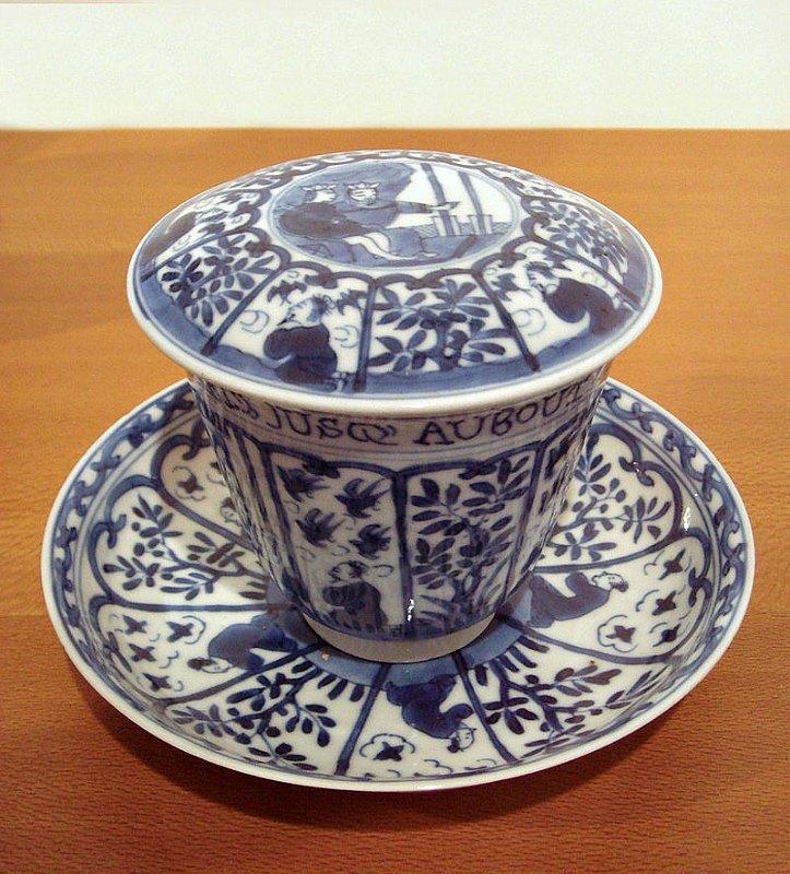 """Porcelana china blanca y azul para la exportación, con escena europea e inscripción en francés: """"El Imperio de la Virtud está establecido hasta los confines del Universo"""". Periodo Kangxi (1690-1700). Museo Guimet de París, Francia. (World Imaging/CC BY-SA 3.0)"""