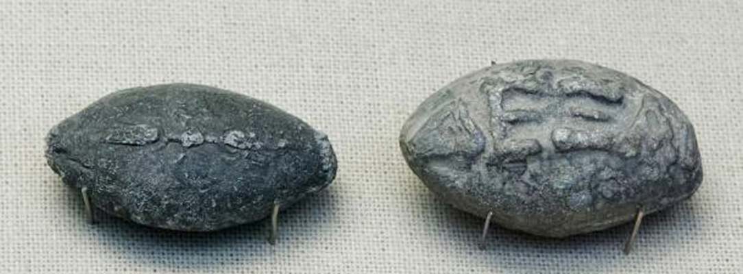 """Proyectiles de honda de la antigua Grecia con inscripciones. En una de las caras aparece un rayo alado, y en la otra, escrito en griego, """"chúpate esa"""", en relieve. ( Wikimedia Commons )"""