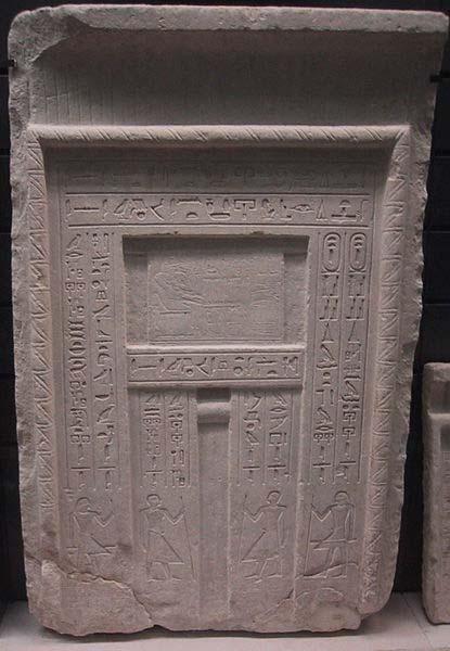 Típica puerta falsa de una tumba egipcia – se puede observar la imagen del difunto por encima del nicho central frente a una mesa con ofrendas, y a lo largo de los paneles laterales hay talladas inscripciones con una lista de ofrendas para el difunto. (CC BY SA 3.0)