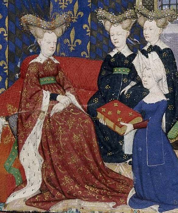 """Christine de Pisan presenta su libro a la reina Isabeau de Francia. Tanto ella como sus damas lucen """"bourrelets"""" enjoyados con forma de corazón sobre un peinado que se asemeja a cuernos. Christine, por su parte, lleva puesto un hennin de dos puntas cubierto por una tela blanca. (Public Domain)"""