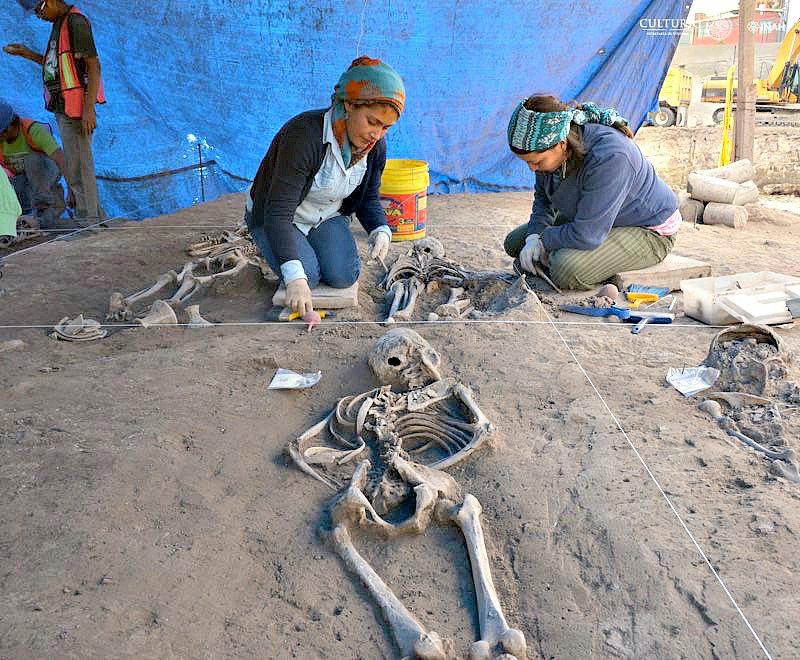 Dos miembros del equipo científico realizando labores de campo junto al esqueleto de un bebé. (Fotografía: Melitón Tapia/INAH)