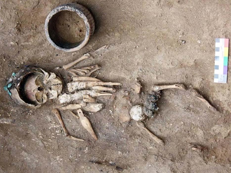 Restos de un niño de corta edad descubiertos en un túmulo funerario de hace 4.500 años junto con ocho figuritas que presentan complejos grabados. También se encontró cubriendo la cabeza del niño un casco metálico hecho con 11 placas de cobre unidas entre sí. Fotografía cortesía de Yury Esin.